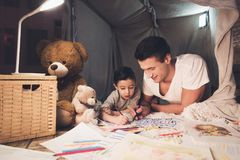 Father and son are drawing with color pencils on paper at night at home. Father and son are drawing with color pencils on paper in blanket fort at night at home Stock Photography