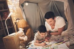Father and son are drawing with color pencils on paper at night at home. Father and son are drawing with color pencils on paper in blanket fort at night at home Royalty Free Stock Photography