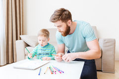 Father and son drawing in living room at home. Father and son sitting and drawing in living room at home Royalty Free Stock Images