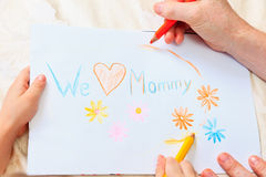 Father and son drawing present for mother Royalty Free Stock Image