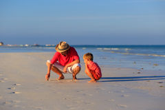 Father and son drawing on summer beach Royalty Free Stock Photos