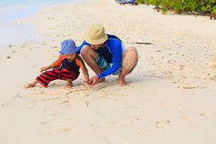 Father and son drawing sun on the beach Royalty Free Stock Photo