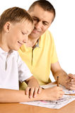 Father and son. Are drawing together with pencil at table Royalty Free Stock Images