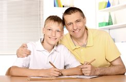 Father and son. Are drawing together with pencils at table Royalty Free Stock Images