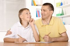 Father and son. Are drawing together with pencils at table Stock Photo