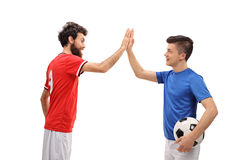 Father and son dressed in sport jerseys high fiving. Each other isolated on white background royalty free stock photography
