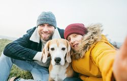 Father and son dressed in warm clothes taking a selfie photo with their best family member beagle dog royalty free stock photo