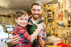 Father and son with drill working at workshop Stock Photo