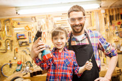 Father and son with drill working at workshop Stock Photography