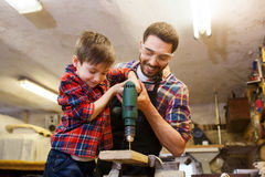 Father and son with drill working at workshop Royalty Free Stock Images
