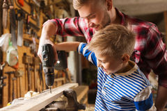Father and son with drill working at workshop Royalty Free Stock Photography