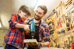 Father and son with drill working at workshop Royalty Free Stock Photo