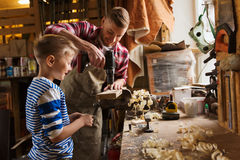 Father and son with drill working at workshop Stock Image