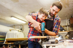 Father and son with drill working at workshop. Family, carpentry, woodwork and people concept - father and little son with drill perforating wood plank at Royalty Free Stock Photo