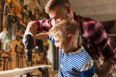 Father and son with drill working at workshop. Family, carpentry, woodwork and people concept - father and little son with drill perforating wood plank at Royalty Free Stock Photography