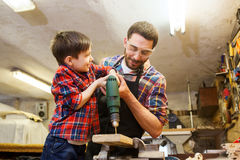 Father and son with drill working at workshop. Family, carpentry, woodwork and people concept - father and little son with drill perforating wood plank at Stock Photography