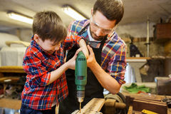 Father and son with drill working at workshop. Family, carpentry, woodwork and people concept - father and little son with drill perforating wood plank at Royalty Free Stock Images