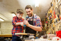 Father and son with drill working at workshop. Family, carpentry, woodwork and people concept - father and little son with drill perforating wood plank at Royalty Free Stock Photos