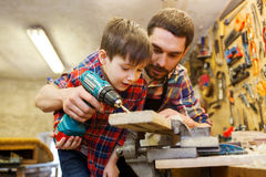 Father and son with drill working at workshop. Family, carpentry, woodwork and people concept - father and little son with drill perforating wood plank at Stock Images