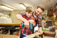 Father and son with drill working at workshop Stock Photos