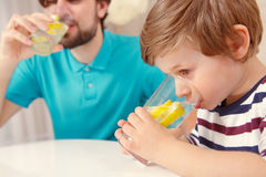 Father and son drink lemonade Stock Photo