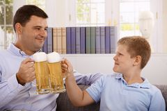 Father and son drinking beer smiling. Father and son drinking beer, clinking with glasses, smiling Stock Photo