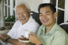Father and son drinking coffee outdoors (portrait) Royalty Free Stock Photos
