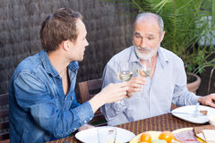 Father and son drinking wine Royalty Free Stock Image