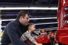 Father with son driving motorbike toy Royalty Free Stock Image