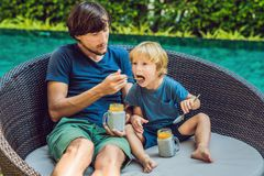 Father and son eat dessert with chia seeds and mangoes by the po. Ol in the morning. healthy eating, vegetarian food, diet and people concept Stock Photos