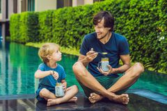 Father and son eat dessert with chia seeds and mangoes by the po. Ol in the morning. healthy eating, vegetarian food, diet and people concept Royalty Free Stock Photo