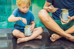 Father and son eat dessert with chia seeds and mangoes by the po. Ol in the morning. healthy eating, vegetarian food, diet and people concept royalty free stock image