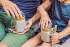 Father and son eat dessert with chia seeds and mangoes by the po. Ol in the morning. healthy eating, vegetarian food, diet and people concept stock photo