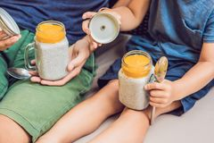 Father and son eat dessert with chia seeds and mangoes by the pool in the morning. healthy eating, vegetarian food, diet. And people concept royalty free stock photo