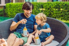 Father and son eat dessert with chia seeds and mangoes by the pool in the morning. healthy eating, vegetarian food, diet. And people concept Royalty Free Stock Image