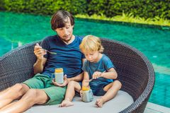 Father and son eat dessert with chia seeds and mangoes by the pool in the morning. healthy eating, vegetarian food, diet. And people concept Royalty Free Stock Photos