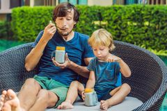 Father and son eat dessert with chia seeds and mangoes by the po. Ol in the morning. healthy eating, vegetarian food, diet and people concept Stock Photography