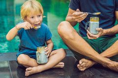 Father and son eat dessert with chia seeds and mangoes by the pool in the morning. healthy eating, vegetarian food, diet. And people concept stock photos