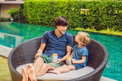 Father and son eat dessert with chia seeds and mangoes by the pool in the morning. healthy eating, vegetarian food, diet. And people concept stock photo