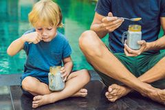 Father and son eat dessert with chia seeds and mangoes by the pool in the morning. healthy eating, vegetarian food, diet and peopl. E concept royalty free stock photos