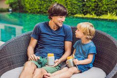 Father and son eat dessert with chia seeds and mangoes by the pool in the morning. healthy eating, vegetarian food, diet and peopl. E concept stock images