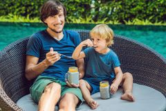 Father and son eat dessert with chia seeds and mangoes by the pool in the morning. healthy eating, vegetarian food, diet and peopl. E concept stock photo