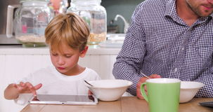 Father And Son Eating Breakfast Whilst Using Digital Tablets. Father and son sit at table eating breakfast whilst both using digital tablets.Shot on Sony FS700 stock footage
