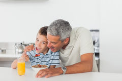 Father and son eating cereal together during breakfast Stock Image