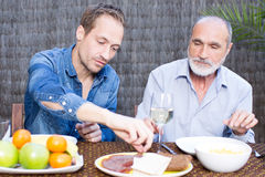 Father and son eating in having snacks in garden. Father and son in garden drinking wine Stock Images
