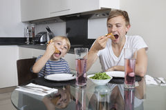 Father and son eating pizza at breakfast table Stock Photo