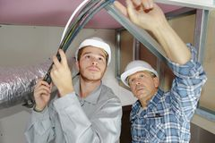 Father and son electricians working on buildings ceiling. 2 stock photos