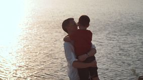 Father with son on shore of lake. Father and son embrace on the shore of a lake on a rock stock footage