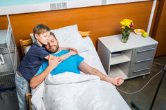 Father with son embracing while laying on hospital bed at ward Royalty Free Stock Photo
