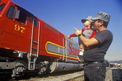 A father and son in engineer caps look at a historic Santa Fe diesel train in Los Angeles, CA Royalty Free Stock Photos